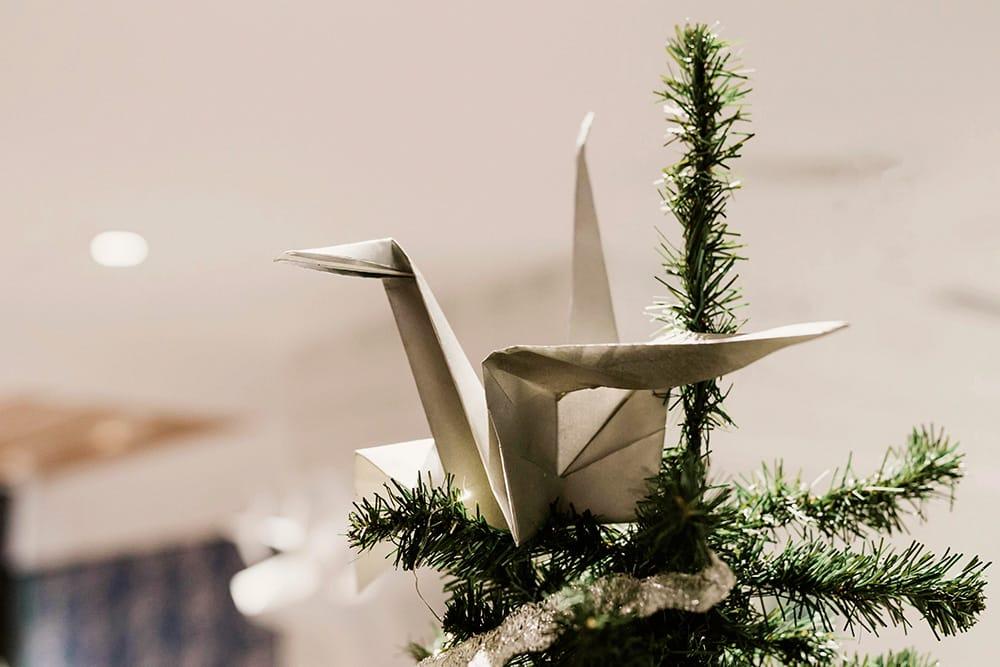 Grulla gigante plateada coronando el árbol de navidad