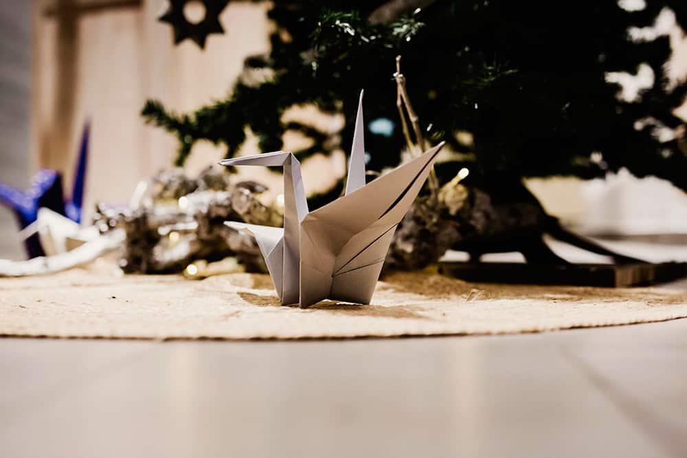 Detalle grulla de origami plateada bajo el árbol de navidad ORIGAMI FOREST