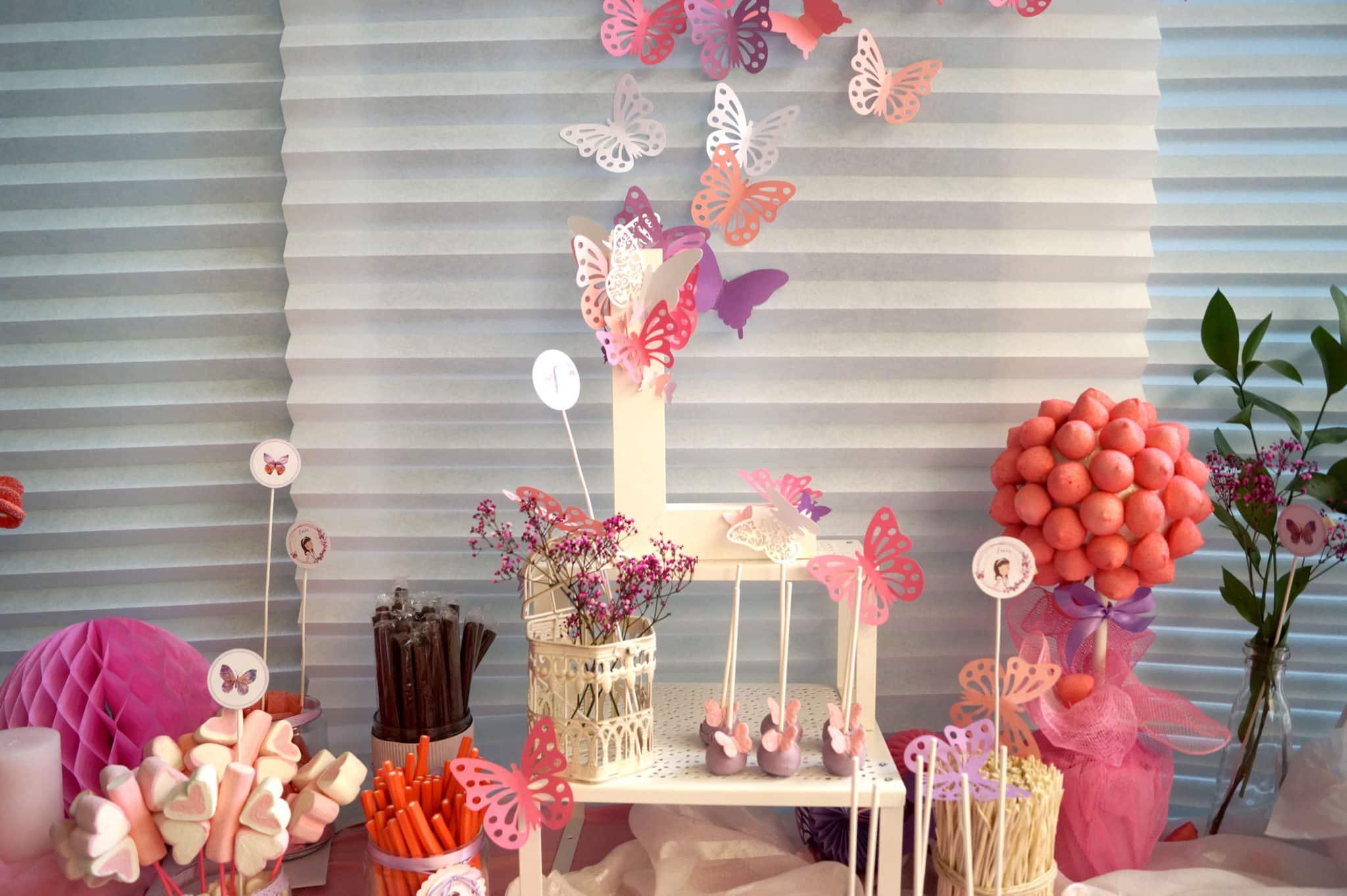 Detalle mesa dulce comunión en tonos rosas y morados con mariposas