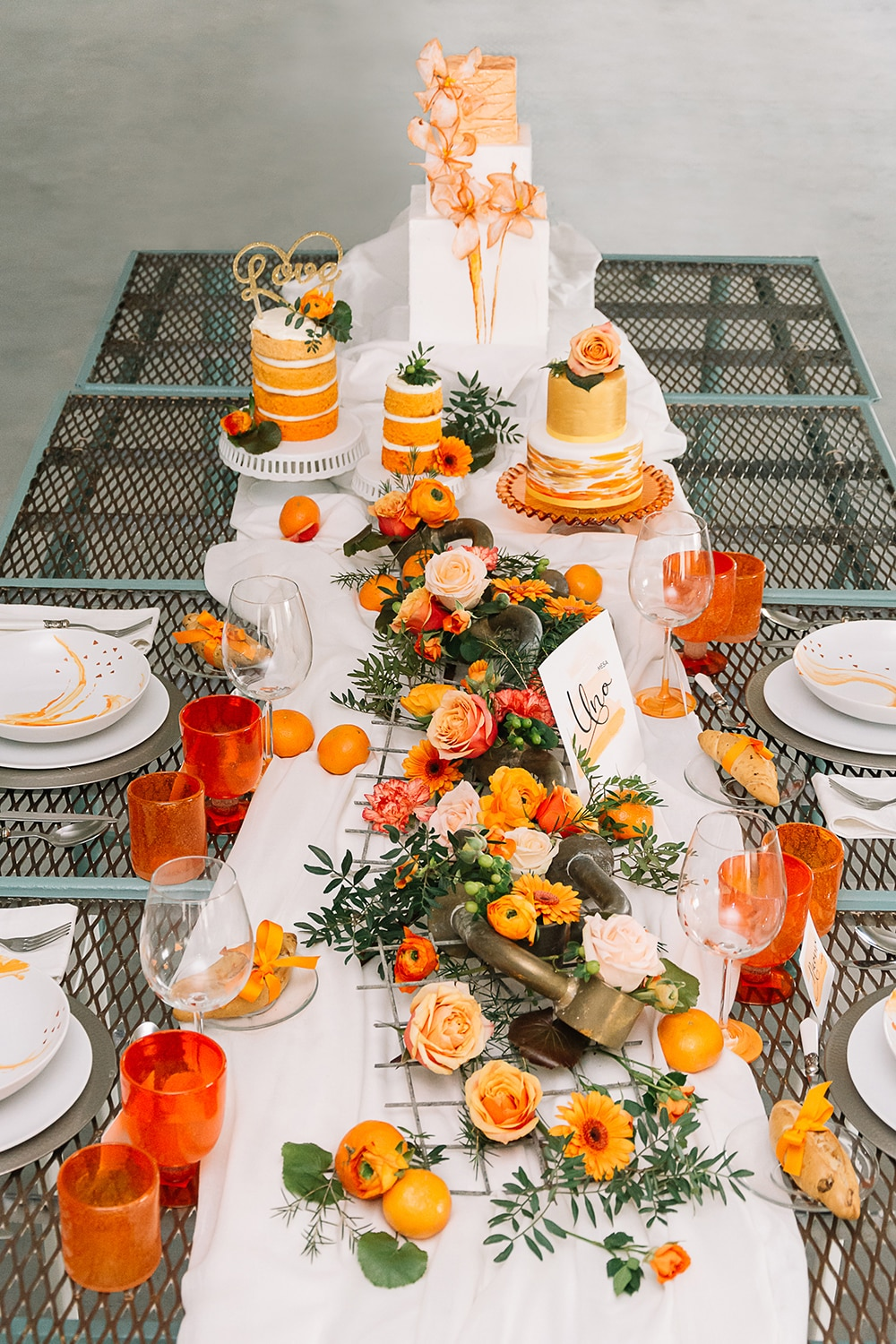 Mesa boda industrial en tonos blancos y naranjas All you need is color en naranja