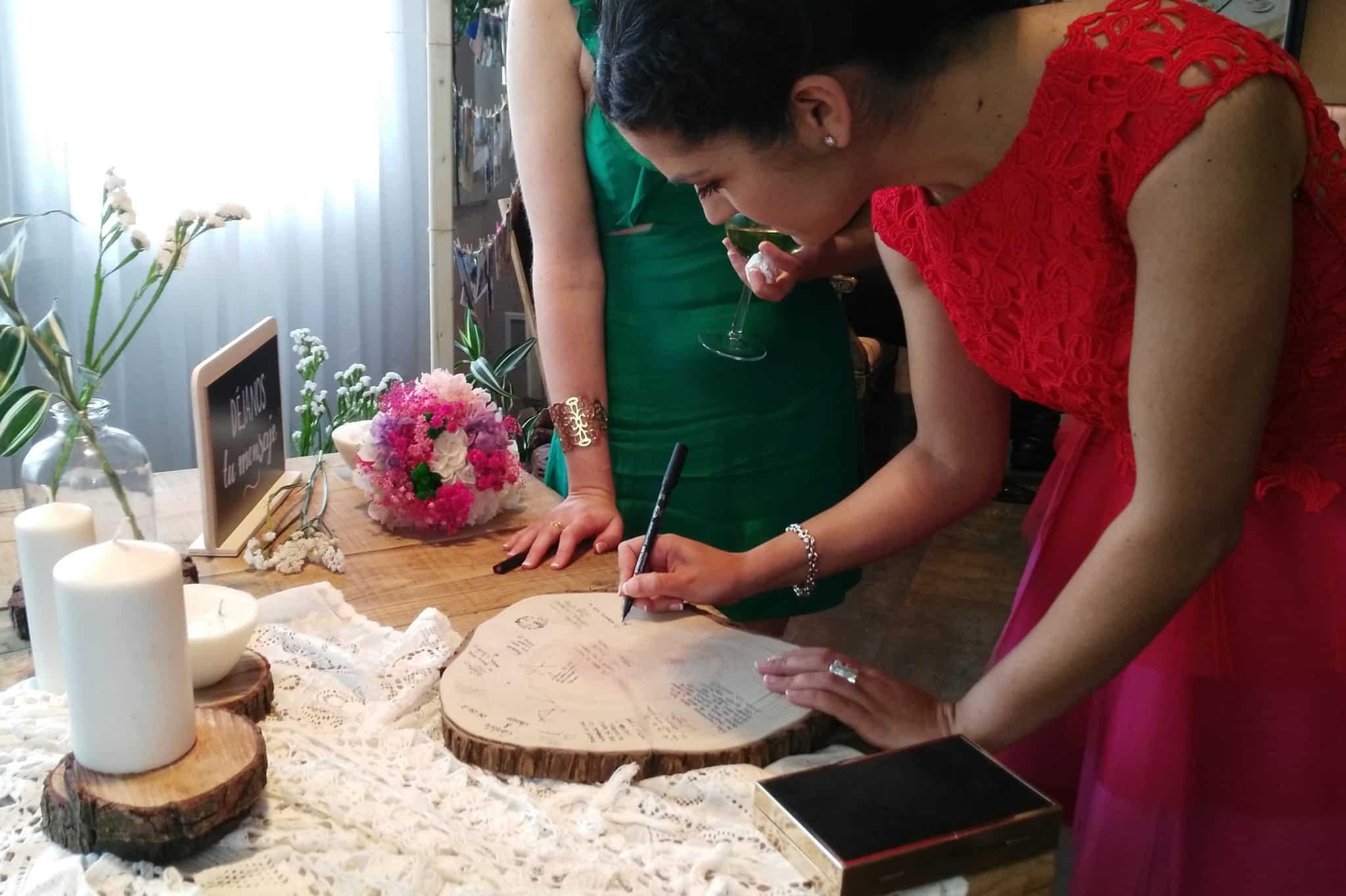 invitadas firmando en una rodaja de madera